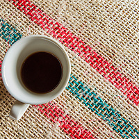 March, 21, 2014 - A cup of fresh black coffee on a bag of beans in the where house where coffee is stored for world-wide shipment at a co-op, Coopertiva de Caficultores de Andes in the town of Jardin in the Department Antioquia region of Colombia.<br /> Story Summary:<br /> Deep in the verdant valleys of Colombia&rsquo;s Department Antioquia region is Fabio Alonso Reyes Cano&rsquo;s coffee finca. Finca La Siemeona has been in Cano&rsquo;s family for generations. <br /> He and two workers farm the 5-acres of land as his ancestors did, bean by bean.  It is a tradition that has dwindled amid modern day farming techniques that harvest quicker but the selectively picked ripe deep red cherries are picked individually by hand for the best quality. &lsquo;Grain by grain&rsquo; processing allows for greater control over that quality of one of Colombia&rsquo;s top exports.  It also may help save an industry that is seeing firsthand the effects of climate change.<br /> Cano takes pride in the organic process, which he practices out of respect for nature and the land he was born and raised on.  A businessman, Cano keeps his eyes on way to grow but he also takes seriously his role as steward, encouraging biodiversity and employing natural pest control on the finca.  His practices are at odds with other coffee farmers, who have adopted more industrialized techniques. <br /> Climate change threatens a way of life that supports about 92,000 families nationwide and serves as one of Colombia&rsquo;s economic backbones.  Colombian coffee production has declined in recent years due to regional climate change associated with global warming as both the average temperatures have risen and an increase in rainfall.  The trend disrupts the specific climate requirements to grow the Coffea Arabica bean, and a way of life. (Credit Image: &copy; Eric Reed/ZUMAPRESS.com)