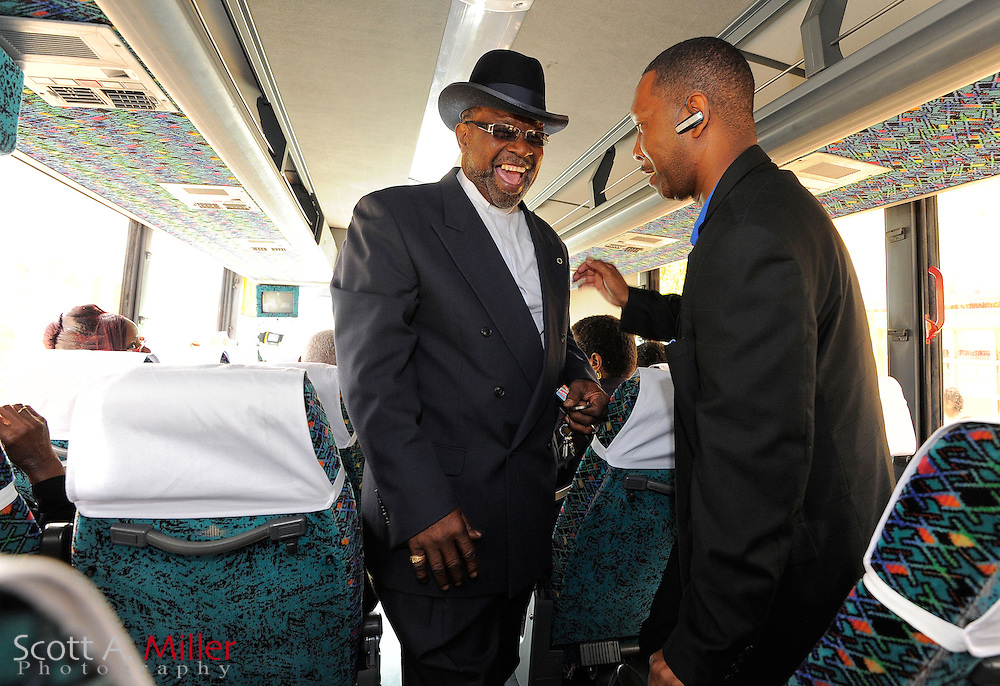 Rev. Errol Thompson, pastor of New Life Fellowship Missionary Baptist Church and Pastor Eddie Walker, of the In Gods Time Tabernacle, share a laugh as they ride the bus to take part in early voting in Orlando, Florida October 20, 2012.  Faith leaders from 44 congregations in six Florida cities led their congregations to early voting locations in a massive ?Souls to the Polls? effort to mobilize faith voters. ©2012 Scott A. Miller.