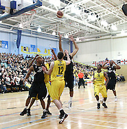 Guildford, England, Sunday 21st March 2010:  Charles Smith of Newcastle jumps behind Colin O'Reilly (12) of Cheshire during the  BBL Trophy Final between Cheshire Jets and Newcastle Eagles at the Guildford Spectrum, Surrey, UK. Final score Cheshire 95-111 Newcastle.  (photo by Andrew Tobin/SLIK images)
