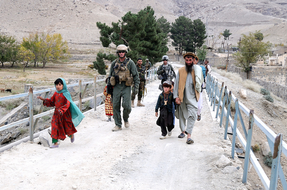 "US Marine Colonel Jeff Haynes, Commanding Officer, 201st Regional Corps Advisory Command, with advisors and Afghan villagers crossing a bridge entering the Tagab Valley.   ....One of the main tactics is a new road through Tagab Valley that will allow traffic to bypass Kabul providing a more direct link between Pakistan and destinations north including Uzbekistan and Tajikistan.....To win the Tagab Valley, Colonel Haynes said, ""The creeping barrage of goodness, really centers on the road going up the valley, because then you can begin development projects and increase prosperity.  The cab fare for villagers went from $8 down to $1 just because the ANA graded the road.""  As the ANA move north through the valley they are building combat outposts to sustain the gains.  Haynes confirmed this is an ANA campaign - the first of its kind - his soldiers are mentoring the ANA, there are no coalition troops.  .."
