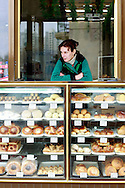 A woman looks to the street from the balcony of a traditional bakery. Azeri GDP grew 41.7% in the first quarter of 2007, possibly the highest of any nation worldwide, as the country economy completed its post-Soviet transition into a major oil based economy.<br /> Baku was awarded the right to host of the first European Games, a multi-sport event.