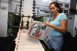 Woman checking Granma newspaper coming off the production line; Havana; Cuba,