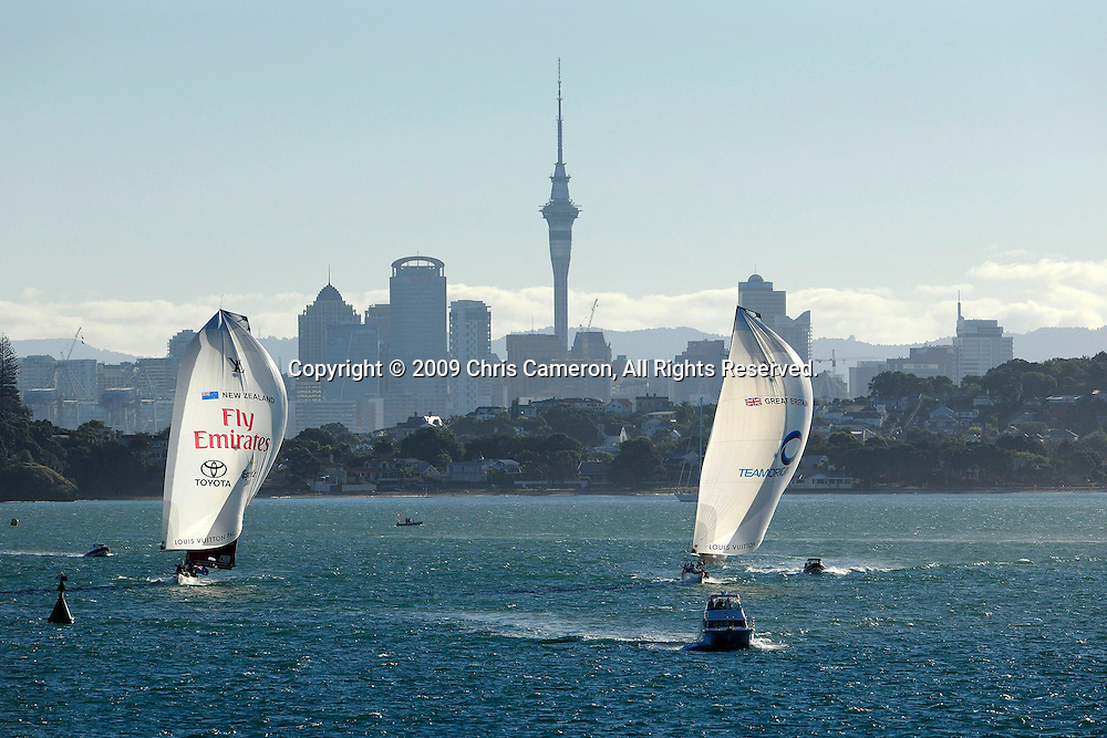 Team Origin and Emirates Team New Zealand with Auckland and North head in the back ground in their Round Robin Two match. Louis Vuitton Pacific Series. 8/2/2009