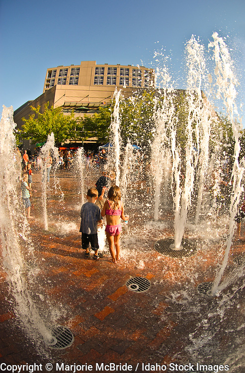 Idaho, Boise.  Children enjoy playing in a water fountain in downtown on a summer evening.