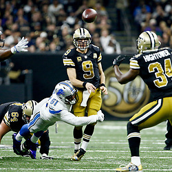 Dec 4, 2016; New Orleans, LA, USA; New Orleans Saints quarterback Drew Brees (9) throws to running back Tim Hightower (34) as he is hit by Detroit Lions defensive end Kerry Hyder (61) during the second quarter of a game at the Mercedes-Benz Superdome. Mandatory Credit: Derick E. Hingle-USA TODAY Sports