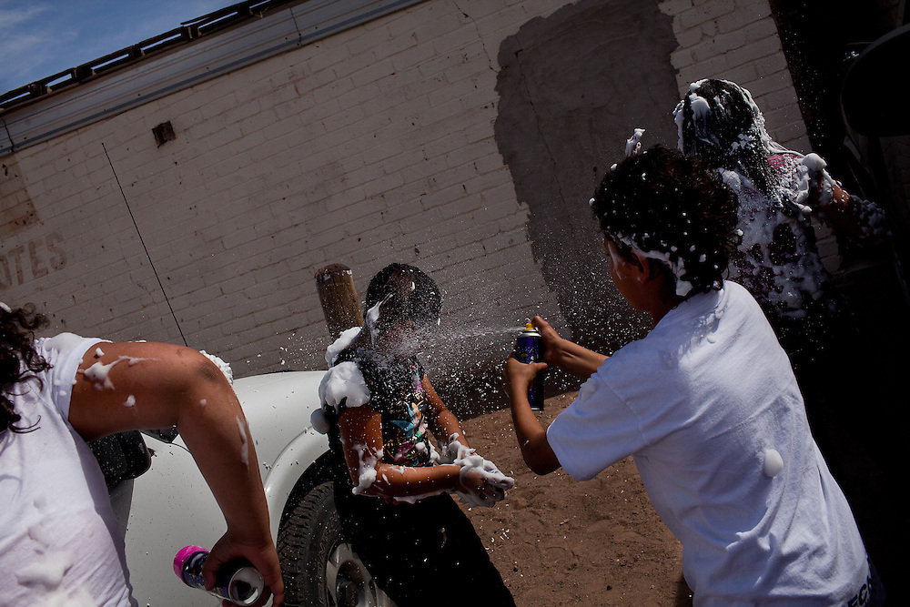 Children spray each other with fake snow in Columbus, New Mexico. Recently federal authorities arrested the mayor, police chief, and trustees who were allegedly operating an illegal gun running ring.