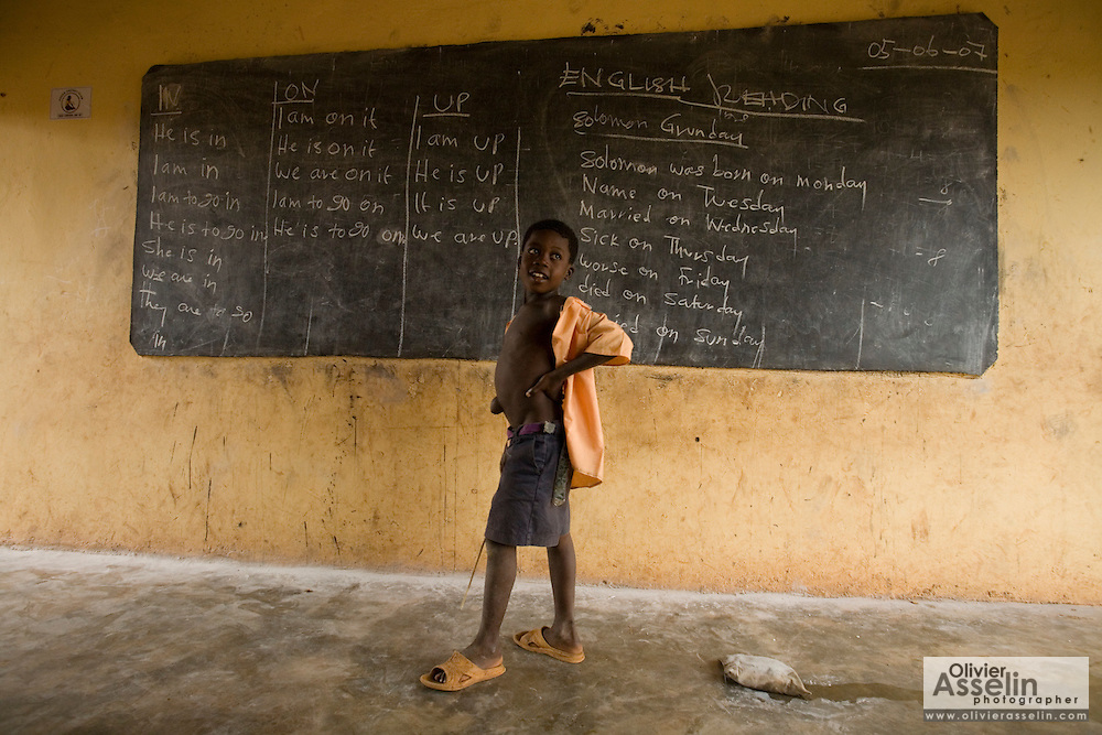 A boy stands in front of a classroom during class at the Nyologu Primary School in the village of Nyologu, northern Ghana, on Wednesday June 6, 2007.