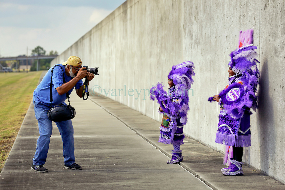 29 August 2015. Lower 9th Ward, New Orleans, Louisiana.<br /> Hurricane Katrina 10th anniversary memorial.<br /> Photographer Eric Waters with L/R; Tia (7 yrs) and Takiera (9 yrs) Augustin of the 9 Red Hawk Mardi Gras Indians at the levee wall which gave way a decade earlier. <br /> Photo credit&copy;; Charlie Varley/varleypix.com.
