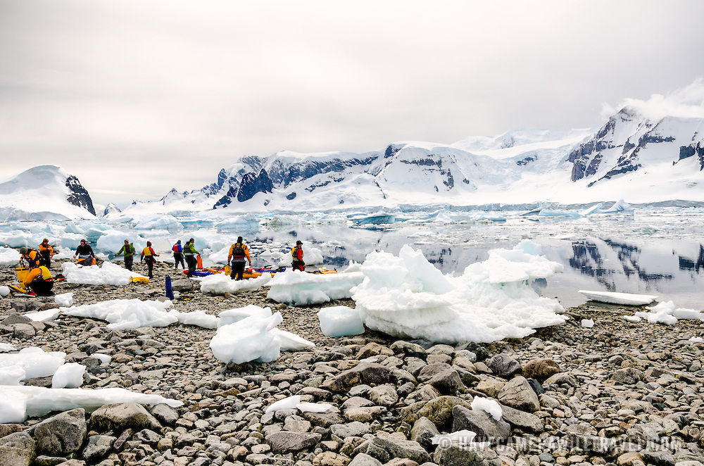 A group of kayakers ashore amongst the rocks and blocks of ice at Cuverville Island on the western side of the Antarctic Peninsula.