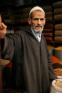 Morocco, Fez. Portrait of a shop keeper at his moroccan spice shop.