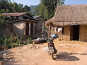house constructed with bamboo; thatched roof; outhouse; dirt yard; motorcycle; Tachilek; Myanmar