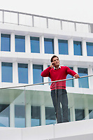Young attractive businessman talking on smartphone in rooftop