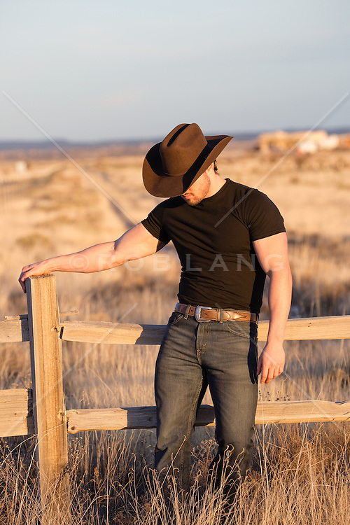 hot cowboy leaning against a split rail fence at sunset
