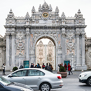 Tourists watch the changing of the guards at Dolmabahçe Palace as busy traffic rushes by. Dolmabahçe Palace, on the banks of the Bosphorus Strait, was the administrative center of the Ottoman Empire from 1856 to 1887 and 1909 to 1922. Built and decorated in the Ottoman Baroque style, it stretches along a section of the European coast of the Bosphorus Strait in central Istanbul.