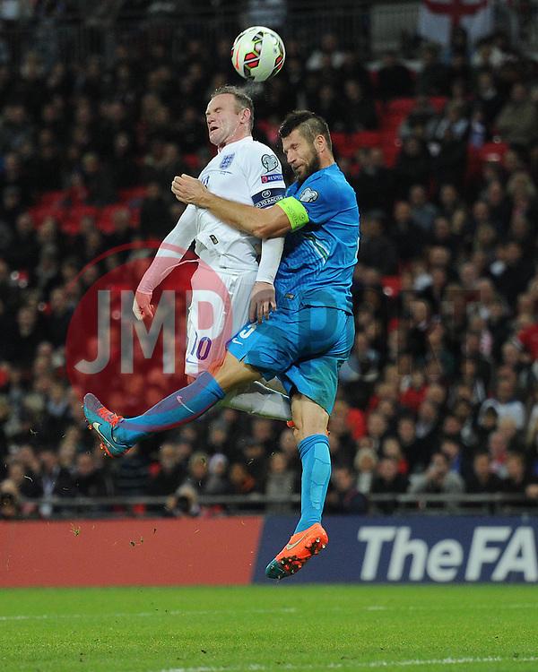 Caption Correction * Wayne Rooney of England (Manchester United) battles for a high ball with Bostjan Cesar of Slovenia   - Photo mandatory by-line: Alex James/JMP - Mobile: 07966 386802 - 15/11/2014 - SPORT - Football - London - Wembley - England v Slovenia - EURO 2016 Qualifier
