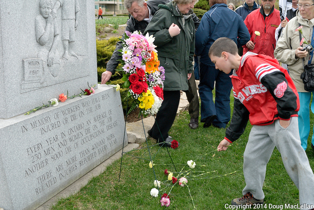 Carnations are laid at the foot of the monument at the 30th annual Workers' National Day of Mourning.