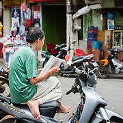 Vietnamese motor taxi driver sitting on bike reading paper while waiting for a fare
