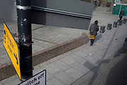 Yellow street signpost and lady wearing yelow and black striped clothing, on 4th March 2019, in London England.