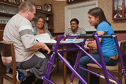 Young white student, who has Cerebral Palsy and uses a walking frame, in multiracial study group.