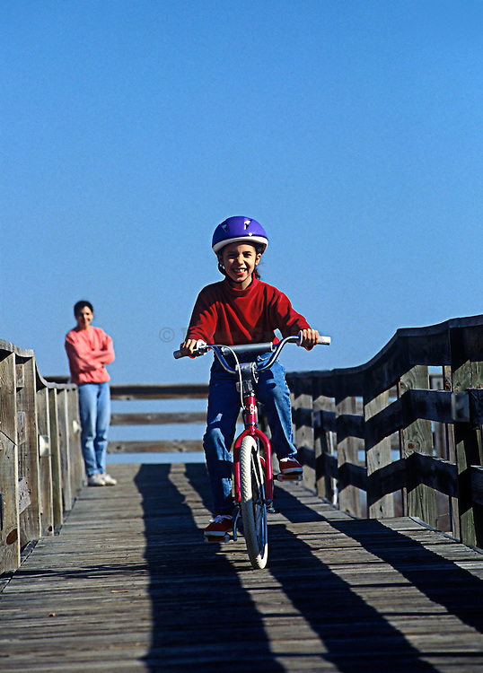 Girl learning how to ride a bike as her mother watches on.