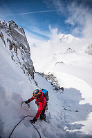 A male mountaineer, as seen venturing up snowy coluoir of Aiguilles Marbrées. In the background a view on Mont Blanc and Pointe Helbroner.