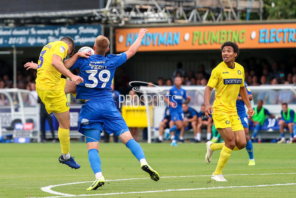Wycombe Wanderers defender Darius Charles (21) watches Wycombe Wanderers defender Joe Jacobson (3) battles for possession with AFC Wimbledon striker Joe Pigott (39) during the EFL Sky Bet League 1 match between AFC Wimbledon and Wycombe Wanderers at the Cherry Red Records Stadium, Kingston, England on 31 August 2019.