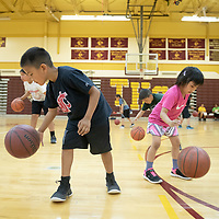 Landon Lee, 7, and sister Audiana Lee, 4, run through their dribbling drills next to one another during the Tohatchi High School Basketball camp in Tohatchi Tuesday.