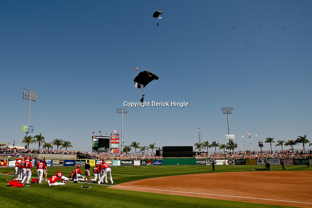 February 27, 2011; Clearwater, FL, USA; Philadelphia Phillies players watch as a parachute trooper lands in the stadium prior to a spring training exhibition game against the New York Yankees at  Bright House Networks Field. Mandatory Credit: Derick E. Hingle