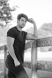 handsome All American man leaning against a rustic fence