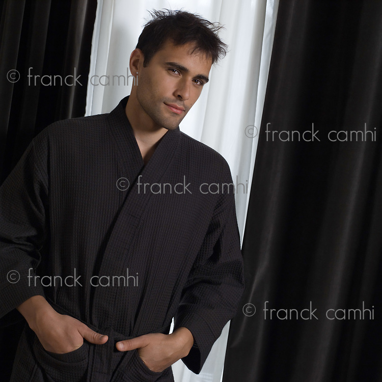portrait of handsome man in a brown bathrobe in front of a window