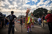 A temple guardian stands beside a busy road during a religious festival.