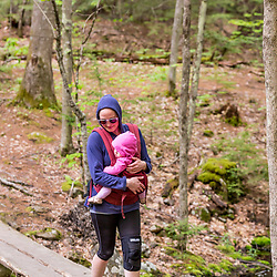 A woman walks with her baby in the woods at the Orris Falls Preserve in South Berwick, Maine.