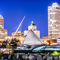 Milwaukee skyline at night photo in blue. Picture includes the Milwaukee lakefront, Milwaukee Art Museum, University Club Tower, and Northwestern Mutual Tower. Photo is high resolution.