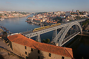 A morning aerial panorama of a tram crossing the Ponte de Dom Luis I bridge with the city of Porto behind on the River Douro and a foreground of warehouse rooftops, on 20th July, in Porto, Portugal. The Dom Luís I (or Luiz I) Bridge is a double-decked metal arch bridge that spans the Douro River between the cities of Porto and Vila Nova de Gaia in Portugal. At the time of construction its span of 172 m was the longest of its type in the world. (Photo by Richard Baker / In Pictures via Getty Images)
