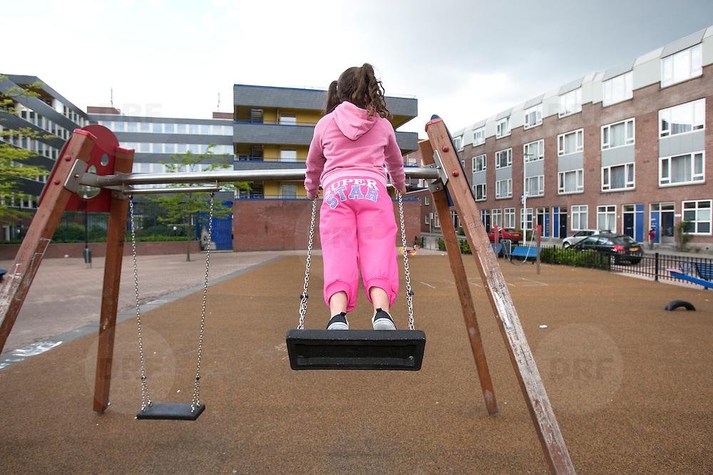 Nederland Rotterdam 18-05-2009 20090518 Foto: David Rozing .                                                                                    .Achterstandswijk Bloemhof, meisje in paarse roze outfit op schommel, op achterkant broek staat Super star, ludiek, ludieke, grappig.Foto: David Rozing/