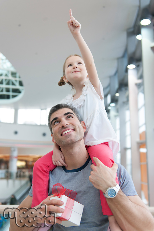 Young daughter points and sits on fathers shoulders