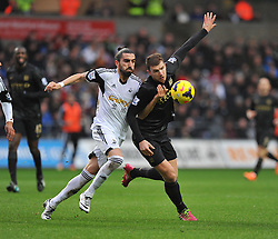 Swansea City's Chico battles hard for the ball with Manchester City's Edin Džeko - Photo mandatory by-line: Alex James/JMP - Tel: Mobile: 07966 386802 01/01/2014 - SPORT - FOOTBALL - Liberty Stadium - Swansea - Swansea City v Manchester City - Barclays Premier League