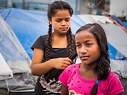 05 AUGUST 2015 - KATHMANDU, NEPAL:  Sisters SUSHILA, 10, (right foreground) and SUSMITA, 13, from Solukhumbu, do their hair in a large Internal Displaced Person (IDP) Camp in the center of Kathmandu. The camp is next to one the most expensive international hotels in Kathmandu. More than 7,100 people displaced by the Nepal earthquake in April live in 1,800 tents spread across the space of three football fields. There is no electricity in the camp. International NGOs provide water and dug latrines on the edge of the camp but the domestic waste water, from people doing laundry or dishes, runs between the tents. Most of the ground in the camp is muddy from the running water and frequent rain. Most of the camp's residents come from the mountains in northern Nepal, 8 - 12 hours from Kathmandu. The residents don't get rations or food assistance so every day many of them walk the streets of Kathmandu looking for day work.     PHOTO BY JACK KURTZ