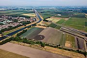 Nederland, Noord Brabant, Gemeente Waalwijk, 08-07-2010. Vroegere  Baardwijksche Overlaat, strook land tussen Waalwijk (links) en Drunen. De autosnelweg A59 ligt hier dan ook laag. ER wordt gesproeid ivm de droogte. Bij hoog water vormde de overlaat een extra afvoer voor het water van de Maas. Aan de horizon de Bergsche Maas waar de overlaat in uitmondde. Links het afwateringskanaal 's-Hertogenbosch - Drongelen. Dit kanaal heeft de overlaat vervangen. .Baardwijksche Overlaat, strip of land between Waalwijk (left) and Drunen, used as spillway (additional outlet for the water of the Meuse). On the horizon the Bergsche Maas..luchtfoto (toeslag), aerial photo (additional fee required).foto/photo Siebe Swart.