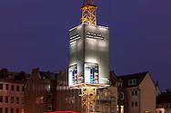 Europa, Deutschland, Nordrhein-Westfalen, Koeln, Baustelle, Kran der Firma Wolff & Mueller mit Werbeplakaten. Der sogenannte Skycrane ist eine vierseitige, quaderfoermige Verkleidung des Baukrans. Die angebrachten Werbeplakate sind hinterbeleuchtet und ergeben eine Gesamtflaeche von ca. 290 Quadratmetern, Werbung fuer ein BlackBerry Smatphone. - ..Europe, Germany, North Rhine-Westphalia, Cologne, construction site, crane of the company Wolff & Mueller with  advertisement. The so called Skycrane is a cuboidal casing of the crane. The mounted billboards are lit behind and produce an area of approximately 290 square meters, promotion for a BlackBerry Smartphone.