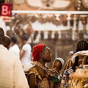A woman carrying her child walks through a pavilion at the 22nd Salon International de l'Artisanat de Ouagadougou (SIAO) in Ouagadougou, Burkina Faso on Saturday November 1, 2008.