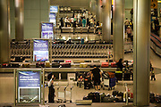 "Seen from an aerial walkway, we look down on airline passengers awaiting the arrival of their baggage in the baggage reclaim hall in the arrivals of Heathrow Airport's Terminal 5. 50-70,000 pieces of British Airways baggage a day travel through 11 miles of conveyor belts which were installed in a 5-storey underground hall beneath the 400m (a quarter of a mile) length of Terminal 5. T5 alone has the capacity to serve around 30 million passengers a year and was completed in 2008 at a cost of £4.3bn. The system was designed by an integrated team from the airport operator BAA, BA and Vanderlande Industries of the Netherlands, and handles both intra-terminal and inter-terminal luggage. From writer Alain de Botton's book project ""A Week at the Airport: A Heathrow Diary"" (2009)."