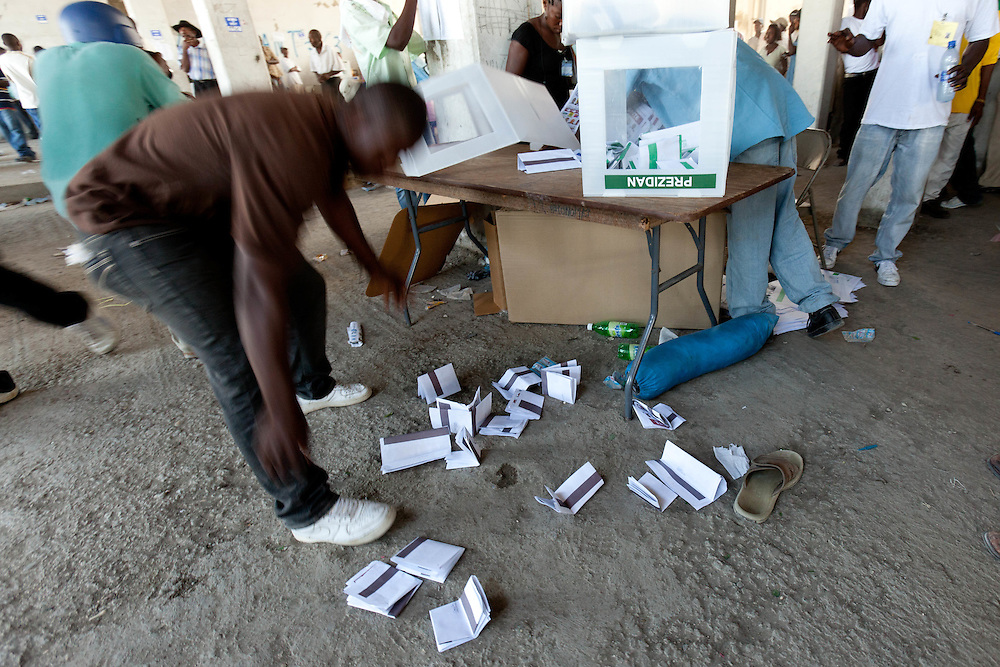 A man picks up cast ballots after a stampede in the voting center which happened when Michel Martelly supporters entered a voting station chanting and marching. Ballot boxes were smashed and ballots lost during the chaos.