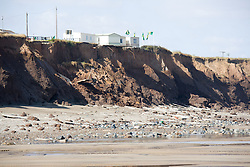 Buildings precariously balanced on edge of eroded cliffs at Tunstall; East Yorkshire; England