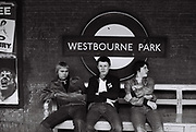 Three teenage friends sit on a bench on Westbourne park station with station sign.