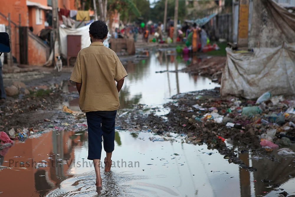 A resettled dalit man walks through a sewage flooded street inside the Tamil Nadu Slum Clearance Board quarters 20 kms away  in Kannagi Nagar in Chennai, India, on Friday, January 14, 2011. Photographer: Prashanth Vishwanathan/HELSINGIN SANOMAT