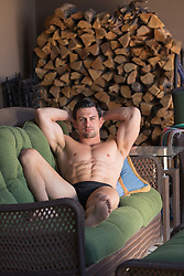 shirtless muscular man in boxer briefs at home
