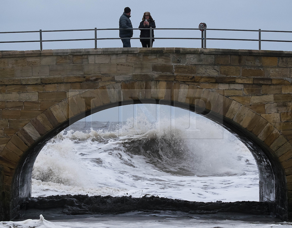 © Licensed to London News Pictures. <br /> 21/03/2015. <br /> <br /> Sandsend, North Yorkshire.<br /> <br /> A couple stand on a bridge crossing Sandsend Beck as waves crash against the sea wall behind them at Sandsend in North Yorkshire. The exceptionally high Spring tides were created by the moon's 18-year cycle.<br /> <br /> Photo credit : Ian Forsyth/LNP