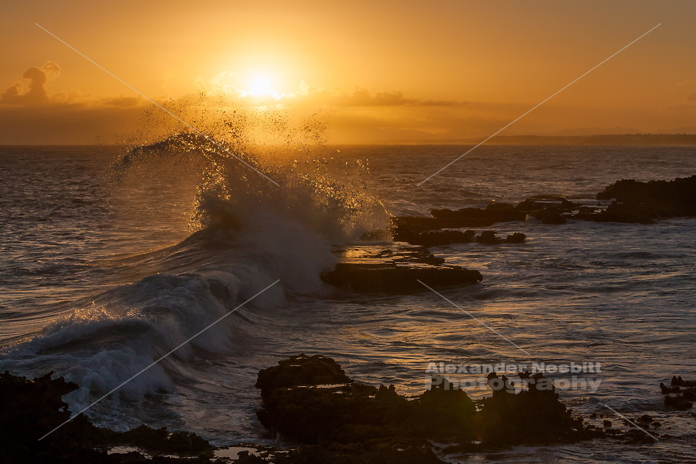 A wave breaks perfectly through the sunset on the caribbean island of Guadeloupe.