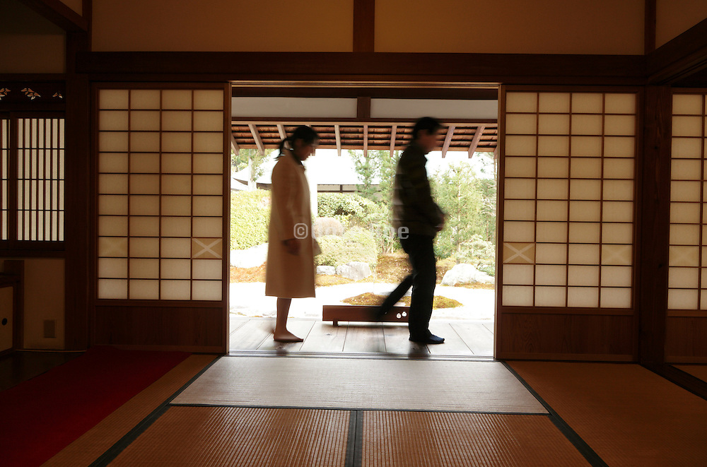 man and woman passing by the door opening of a traditional Japanese house